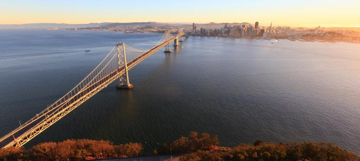 The West Span of the Bay Bridge stretches from Yerba Buena Island in the foreground to San Francisco in the background as the sun rises.