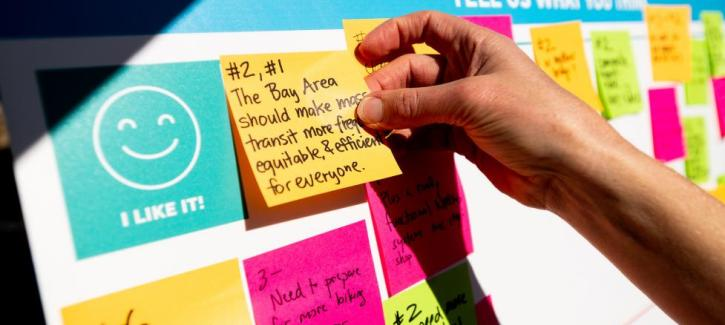 A hand places a Post-it note with comments on a display board at the Excelsior Sunday Streets event.