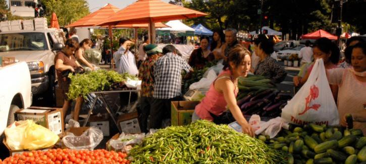 Residents shop at the Santa Rosa Farmers' Market, with piles of tomatoes, cucumbers and peppers in the foreground.