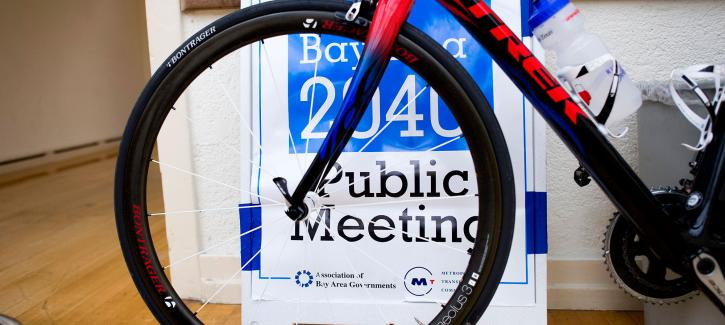 A Plan Bay Area 2040 Public Meeting sign is visible through the spokes of a bicycle tire.