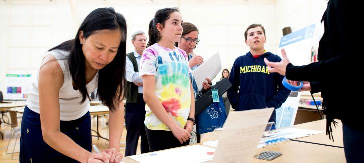 A woman writes down information while two children speak to staff at a Plan Bay Area 2040 open house in Burlingame in 2016.