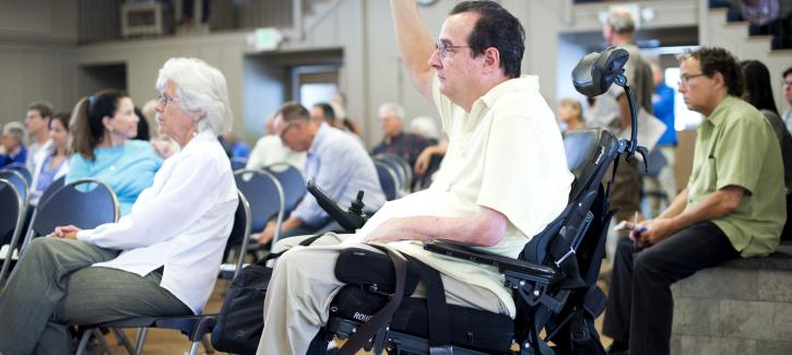 A man in a wheelchair raises his hand to ask a question at the Plan Bay Area 2040 open house in Marin County in 2016.