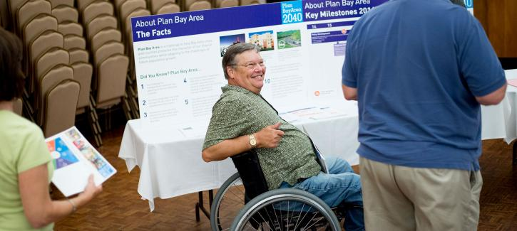 A man in a wheelchair next to a Plan Bay Area 2040 display board.