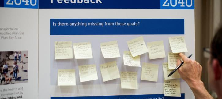 A hand sticks a post-it note to a display board. This board asks questions and residents can respond on the post-it notes.