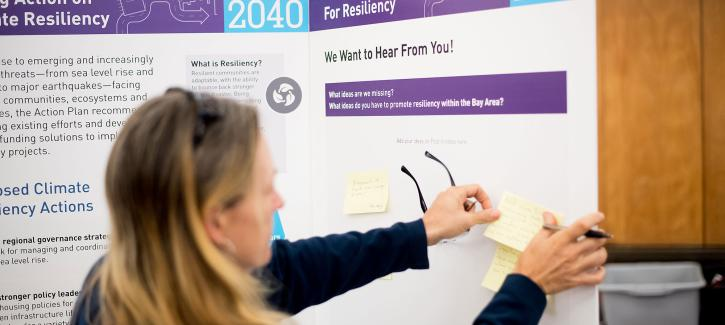 A woman posts a comment note to the resiliency display board at the Plan Bay Area 2040 open house in Napa.