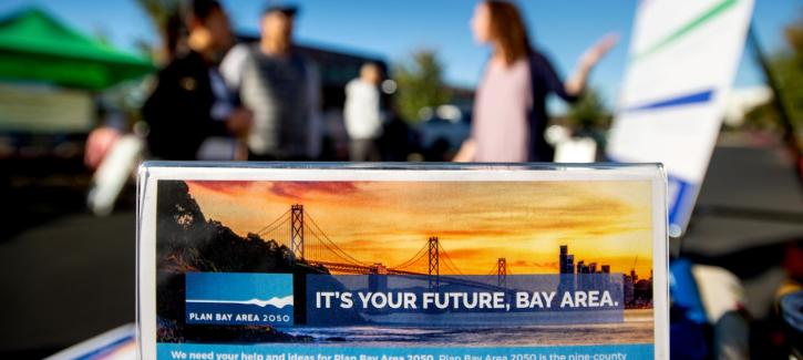 "A tabletop sign reading ""It's Your Future, Bay Area"" with the Plan Bay Area 2050 logo is in the foreground while a staff member speaks with members of the public in the background."