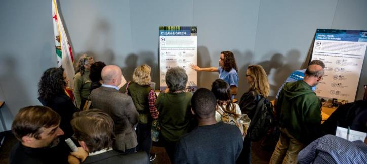 Staff stand near display boards and answer questions from a crowd of attendees at a public workshop.