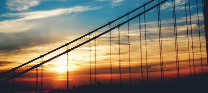The blue sky transitions to yellow, orange and red as the sun sets behind the suspension cables of the Golden Gate Bridge.