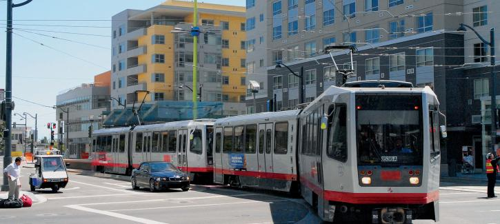 a Muni Metro streetcar glides past compact housing in San Francisco