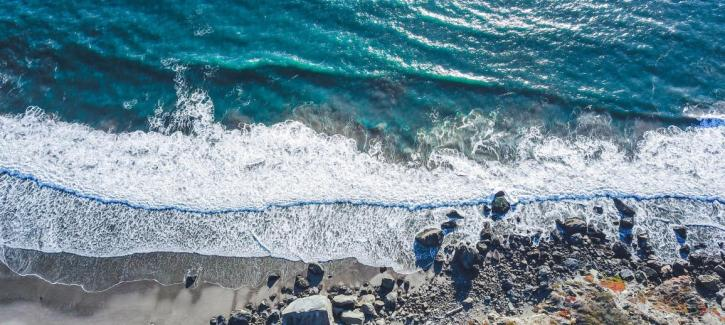 Aerial view of blue waters and white waves crashing against the rocky shore.