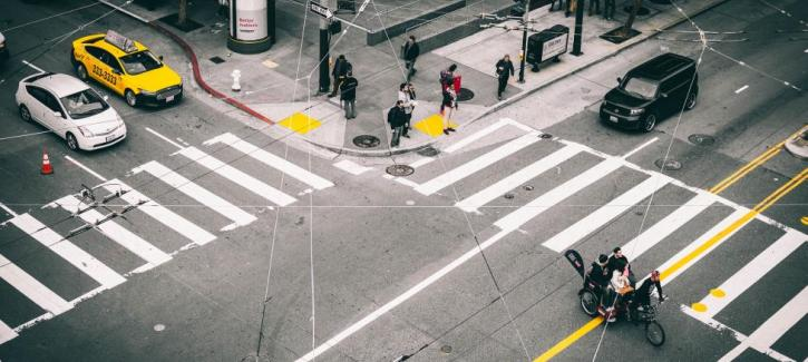Pedestrians wait at the crosswalk, a pedi-cab crosses the intersection, and cars and taxis wait. The view is seen from above through criss-crossing Muni overhead wires.